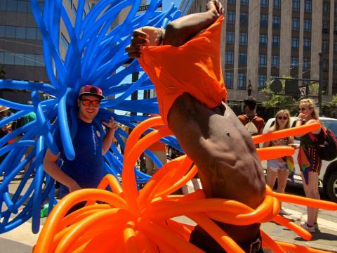 2 jeune hommes avec ballons bleus et oranges à la Gay Pride